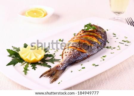 Grilled sea bream fish, lemon, arugula on white plate, horizontal - stock photo