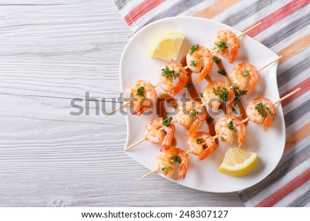 Grilled shrimp on skewers with lemon on a plate. horizontal view from above  - stock photo