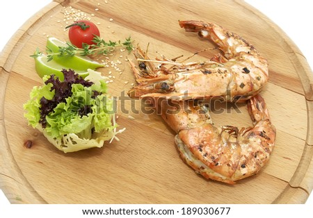 grilled shrimp with a salad on a wooden plate - stock photo