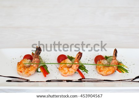 Grilled shrimps line on white plate on light wooden background, flat lay, copyspace for commercials, horizontal position - stock photo