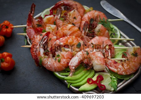 Grilled shrimps on bamboo skewers with fresh avocado and habanero pepper - stock photo