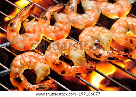 Grilled shrimps on the flaming grill. - stock photo