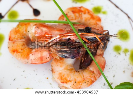 Grilled shrimps on white background, closeup. Three roasted prawns on dish, cooked seafood - stock photo