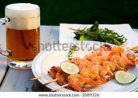 Grilled shrimps on wood sticks served with lime and mug of pale ale - stock photo