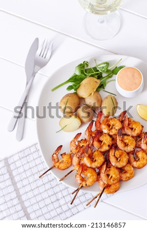 Grilled shrimps with potatoes, sauce and a glass of white wine on a white wooden table - stock photo