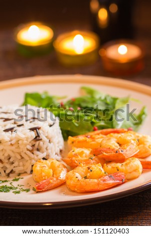 Grilled shrimps with rice in romantic atmosphere - stock photo