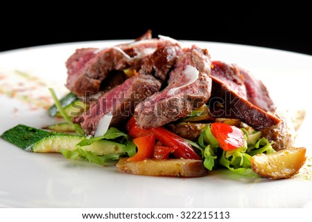 Grilled sliced roast beef on potato and salad - stock photo