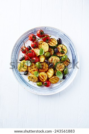 Grilled spiced vegetables with olives on a plate - stock photo