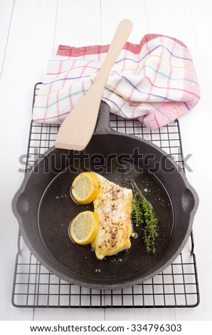 grilled spicy cod with lemon and thyme in a pan - stock photo