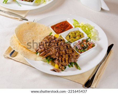 Grilled Steak Fajitas on Plate with Individual Sauces and Garnishes - stock photo