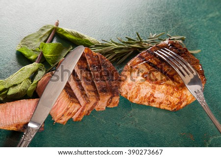 Grilled steak, fork and knife on green background - stock photo
