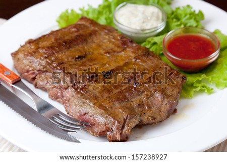 Grilled steak on a white plate - stock photo
