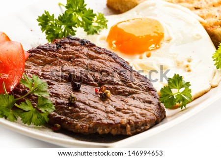 Grilled steak, toast, fried egg and vegetables - stock photo