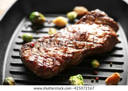 Grilled steak with garlic and Brussels sprouts on grill pan, closeup - stock photo