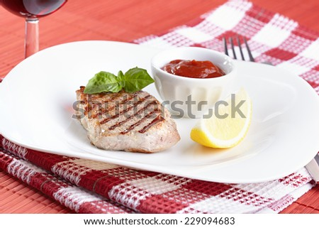 Grilled steak with tomato sauce and a lemon - stock photo