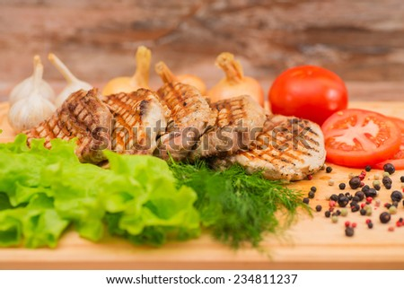 Grilled steak with vegetables on a wooden board. - stock photo