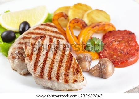 Grilled steak with vegetables on white plate - stock photo