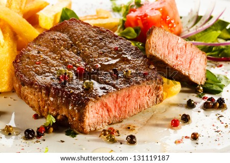 Grilled steaks, French fries and vegetables - stock photo