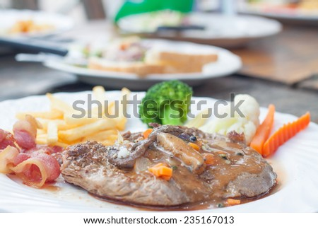Grilled steaks,  French fries, bacon and vegetable - stock photo