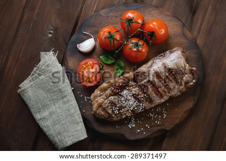 Grilled striploin beefsteak on a rustic chopping board, top view - stock photo
