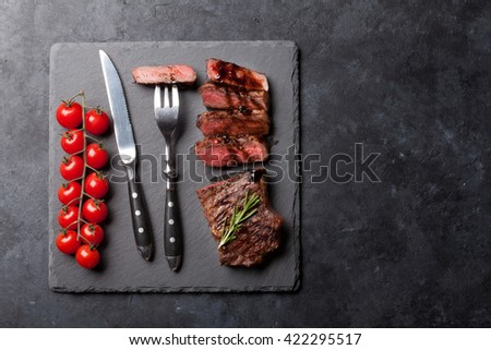 Grilled striploin sliced steak with salt and pepper over stone table. Top view with copy space - stock photo