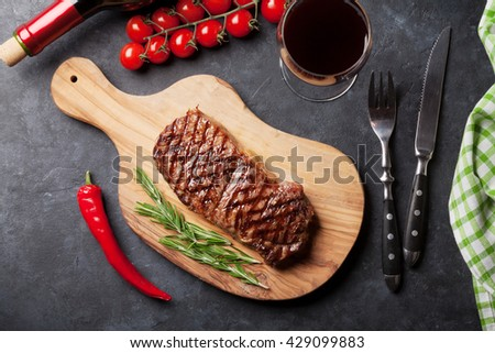 Grilled striploin steak and red wine over stone table. Top view - stock photo