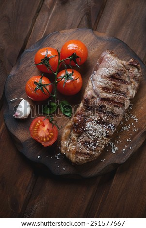 Grilled striploin steak with tomatoes, rustic wooden setting, top view - stock photo