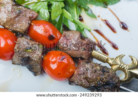 Grilled tenderloin beef kebabs with cherry tomato and potatoes served on a white plate on a wooden table in a restaurant - stock photo