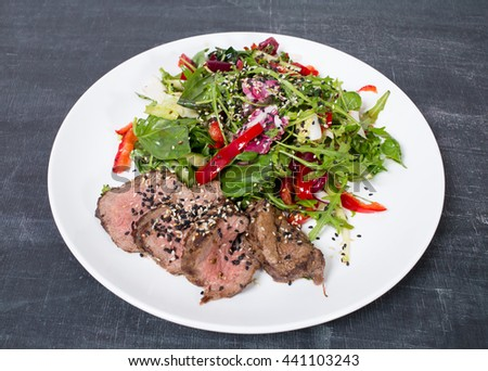 Grilled thai beef salad with fresh herbs. Plate located on a black table as a background. - stock photo