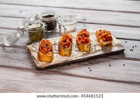 Grilled toasts with vegetables. Salt and pepper in jars. Delicious homemade food. Bruschetta for vegetarians. - stock photo