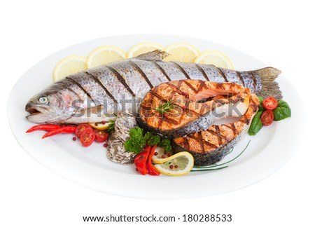 Grilled trout and salmon steak with vegetables and oysters. - stock photo