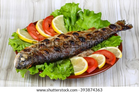 Grilled trout barbeque served lemon, tomato and salad leaves - stock photo