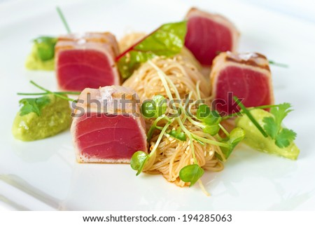 Grilled tuna chunks served with rice noodles and fresh green herbs on white plate. See more food shots  - stock photo