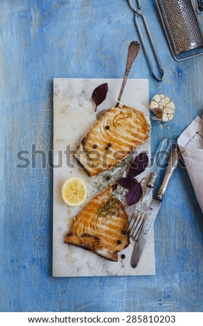 Grilled tuna steak (swordfish) served on marble table over on blue rustic surface  with kitchen tools. Rustic style. - stock photo