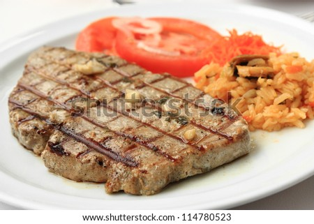Grilled tuna steak with limpets rice and tomatoes. - stock photo