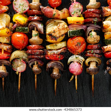 Grilled vegetable and meat skewers  on the black stone background, top view - stock photo