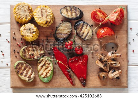 Grilled vegetables on cutting board on white wooden background. Flat lay on vegetable bbq serving. Top view on vegetarian grill set - stock photo