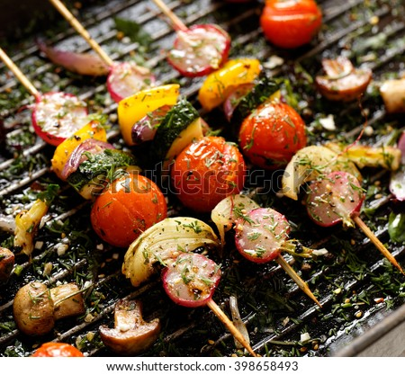 Grilled veggie skewers with cherry tomatoes, radishes, peppers and onions with fresh dill on a grill pan - stock photo