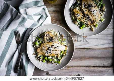 Grilled white fish fillet with mushroom risotto and edamame on rustic background - stock photo