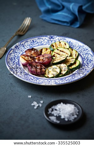 Grilled zucchini and red onion on a plate - stock photo