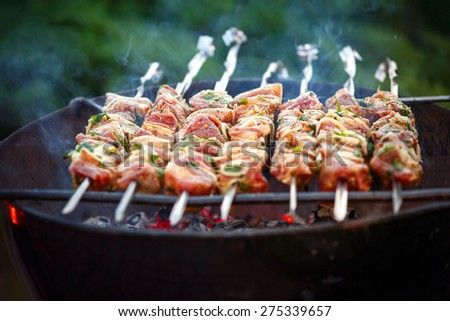 Grilling at summer weekend. Fresh meat preparing on grill. - stock photo