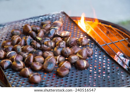 Grilling chestnuts being sold at stalls in autumn. - stock photo