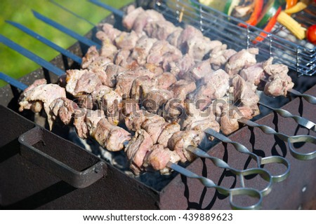 Grilling marinated shashlik on a grill. Shashlik is a form of Shish kebab popular in Eastern, Central Europe and other places. Shashlyk (meaning skewered meat) was originally made of lamb. - stock photo
