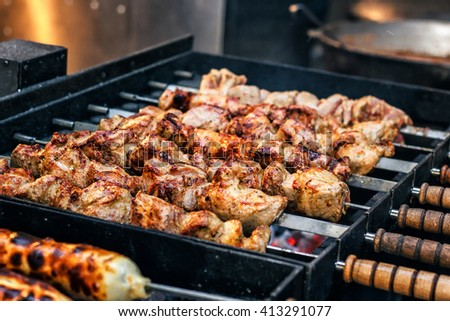 Grilling marinated shashlik preparing on a barbecue grill over charcoal. Shashlik is a form of Shish kebab popular in Eastern Europe. Shashlyk (meaning skewered meat) was originally made of lamb. - stock photo