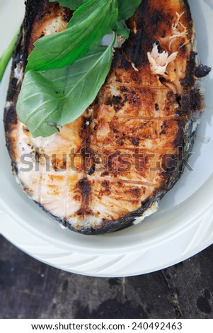 grilling salmon steak with milk cream in grid over barbecue - stock photo