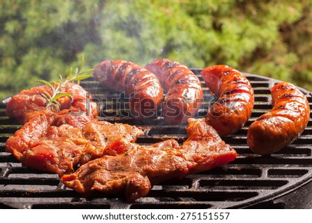 Grilling sausages on barbecue grill. Selective focus. - stock photo