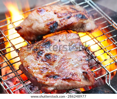 Grilling sirloin steak flame broiled on a barbecue, shallow depth of field.  - stock photo