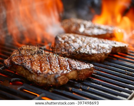 grilling steaks on flaming grill and shot with selective focus - stock photo