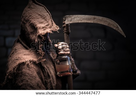 Grim Reaper is holding a bottle of alcohol beverage. The man is standing and threatening with a scythe - stock photo