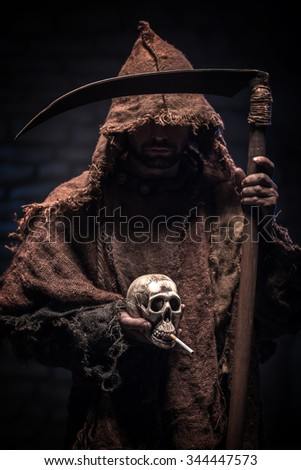 Grim Reaper is holding a scull smoking a cigarette. The man is standing in mantel. He is carrying a scythe with threats - stock photo